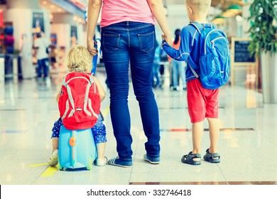 mother and two kids walking in the airport, family travel