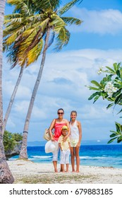 Mother with two kids walking at tropical beach with palms