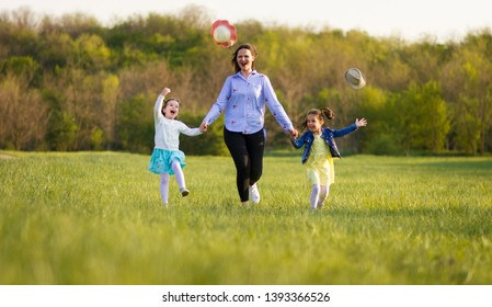 Mother with two little girls,hold them for a hands,running across the sunny meadow. Girls throwing their hats in the air. Female pat of the family outdoor.