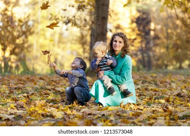 Mother with two sons in the park. Falling maple leaves. Early fall.