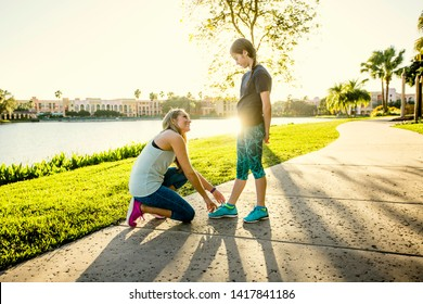 Mother tying the shoe of her daughter before going on a jog together. Showing love and concern while sharing a moment together