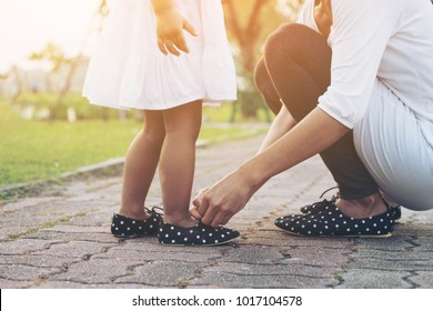 Mother tying shoe  little girl in the park selective focus.