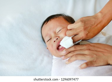 Mother use finger to clean tongue and baby's teeth with clean gauze.