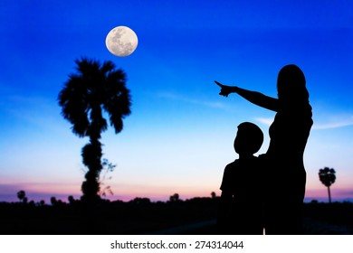 Mother use hand point the full moon on the sky his son see
