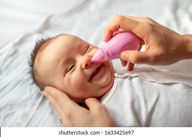 mother using baby nasal aspirator mucus nose suction