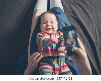 A mother is using her smartphone to take a photo of her baby