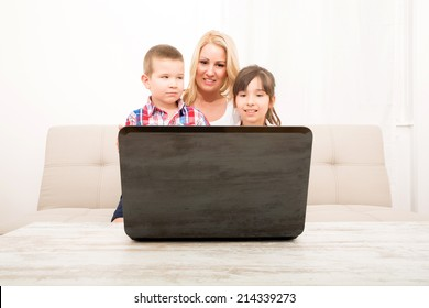 A mother using with her son and daughter a laptop computer.