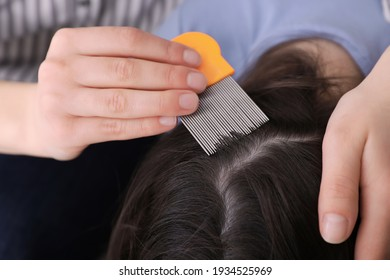 Mother using nit comb on her daughter's hair indoors. Anti lice treatment