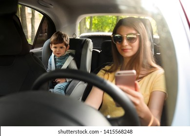 Mother using phone while driving car with her son on backseat. Child in danger