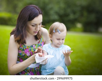 Mother using wet wipes for her daughter on white park background