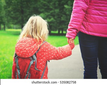 mother walking little daughter to school or daycare
