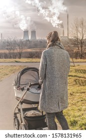 Mother walks with baby carriage during high air pollution. Smog from factory, chimney.