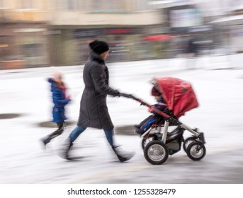 Mother walks with the child in the stroller in snowy winetr day. Intentional motion blur. Defocused image