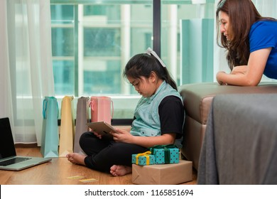 Mother wanting to see daughter playing digital tablet. Social problem between parents and children because of overuse the tablet.