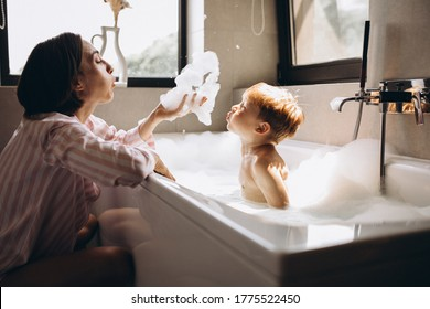 Mother washing little son in bathroom