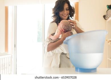 Mother washing a newborn baby in a bath tub