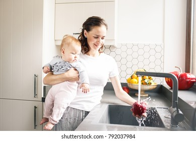 Mother washing pepper while holding a baby