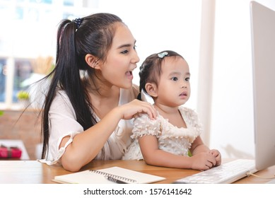 Mother watching her daughter who is learning to use the computer.