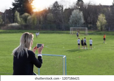 Mother watching or taking photo of her son playing football. Sport, tailgating, active lifestyle, happy family concept