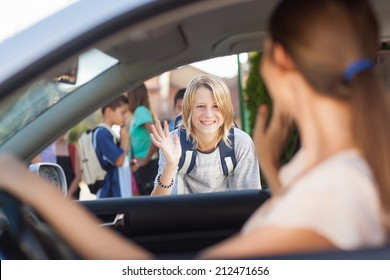 Mother waving goodbye at her son before school.