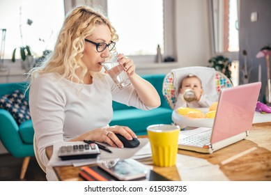 Mother wearing eyeglasses sitting at a desk with her baby and drinking water while she using laptop at home office