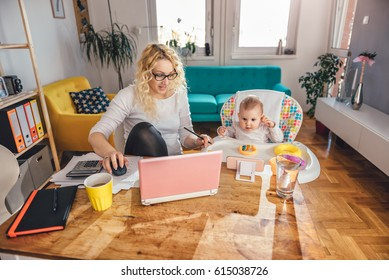 Mother wearing eyeglasses working at home office on laptop and taking care of her baby