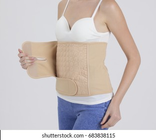 Mother wearing obstetrical support belt on white background