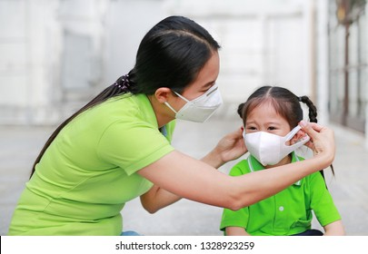Mother wearing protective mask for her daughter while outside to against PM 2.5 air pollution.