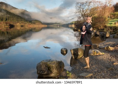 A mother wearing wellington boots stand on lakeside near rocks carries her baby wearing a reindeer hat on her shoulders as both laugh in front the Loch Lemond with low clouds reflected on the lake