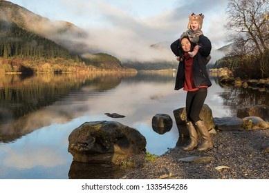 A mother wearing wellington boots standing on lakeside near rocks carries her baby wearing a reindeer hat on her shoulders as both laugh in front of the Loch Lomond