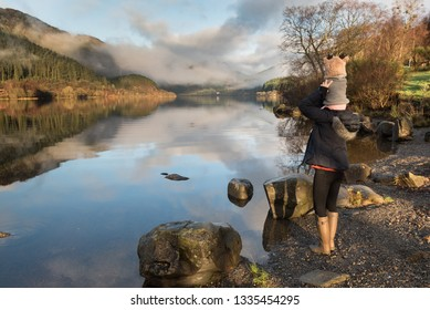A mother wearing wellington boots standing on lakeside near rocks carries her baby wearing a reindeer hat on her shoulders as both glance at the Loch Lomond where low clouds are reflected on the lake'
