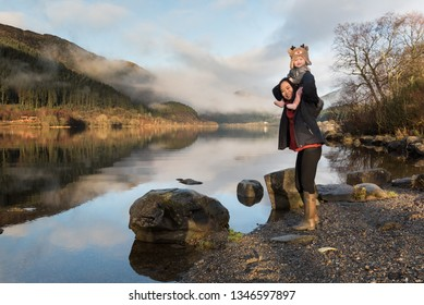 A mother wearing wellington boots standing on lakeside near rocks carrying her baby wearing a reindeer hat on her shoulders as both laugh in front the Loch Lemond