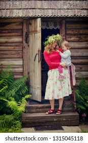 mother wearing wreath with daughter in his arms standing on a doorstep