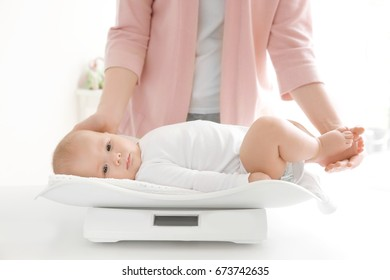 Mother weighing baby on scales in room