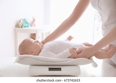 Mother weighting baby on scales in room