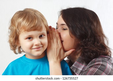 Mother whispers something to her little son