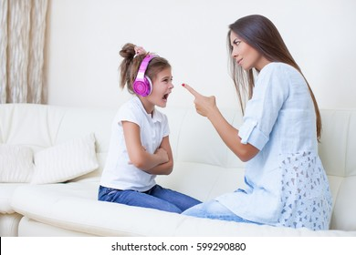 Mother will Raise a Daughter of a Teenage Girl, Girl Screams in Response to Listening to Headphones. Mom Threatens a Finger. Aggressive Teenager. Caucasian woman and girl teen screaming, yelling