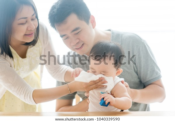 Mother wipes baby nose with tissue paper. Asian family spending quality time at home, living lifestyle indoors.
