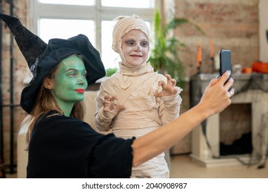 Mother in witch attire making selfie with her son in zombie costume on halloween day