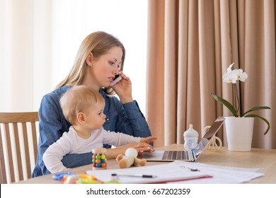 Mother working at home with child in her lap