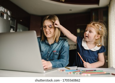 Mother working from home with kid. Quarantine and closed nursery school during coronavirus outbreak. Child make noise and disturb woman at work. Homeschooling and freelance job. Stay at home.