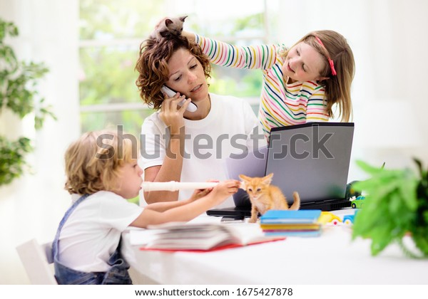 Mother working from home with kids. Quarantine and closed school during coronavirus outbreak. Children make noise and disturb woman at work. Homeschooling and freelance job. Boy and girl playing.