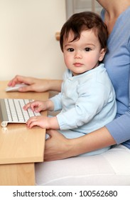 Mother working on computer with baby