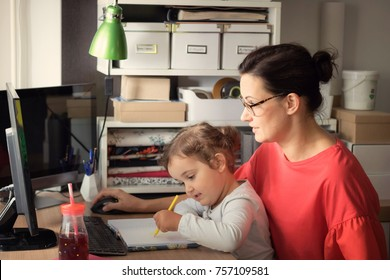 Mother working on desktop PC while daughter is sitting on her lap and drawing on the paper.