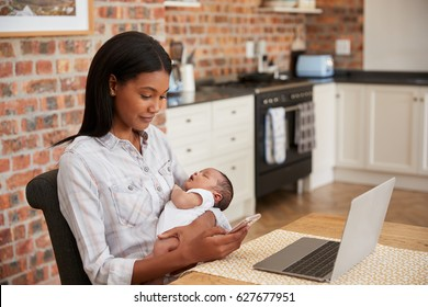 Mother Working On Laptop Holds Newborn Son And Sends Text