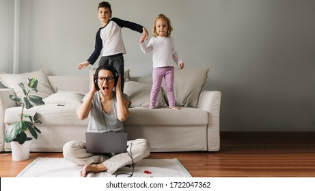 Mother works from home with her children. Quarantine due to coronavirus. Children make noise and disturb a woman at work. Home schooling and work. Boy and girl are dancing