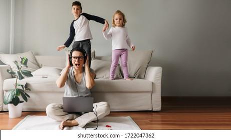 어머니는 자식들과 집에서 일한다.코로나바이러스로 인해 격리되었습니다.아이들은 직장에서 소리를 내고 여자를 방해한다.가정교육과 일들.소년 소녀가 춤을 추고 있다