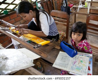 Mother works loom while child does homework in Siem Reap, Cambodia on Oct 11, 2011