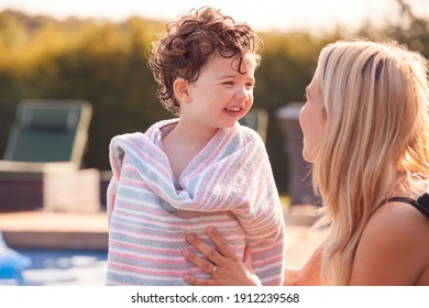 Mother Wrapping Son In Towel By Outdoor Swimming Pool On Summer Vacation