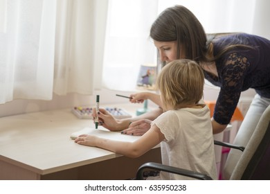Mother writing to teach her daughter